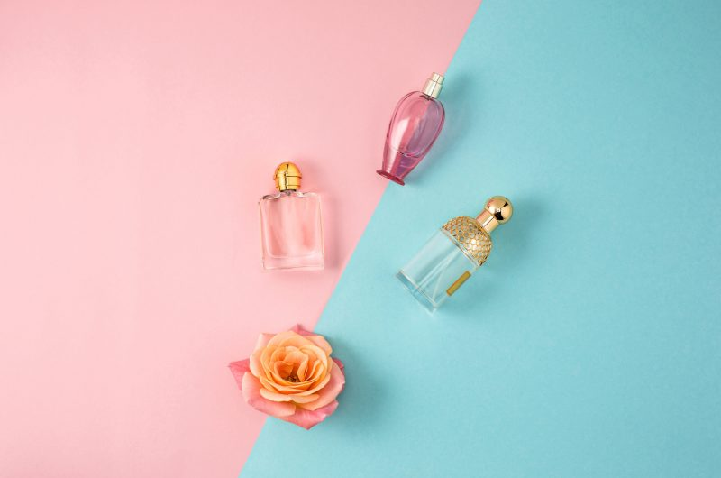 Cosmetics - Perfume on colorful backgroundb with rose
